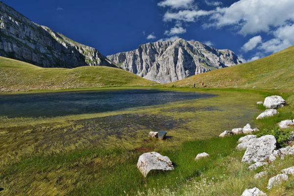 The alpine lake Drakolimni of Tymfi at the green alpine plateau of the mountain.
