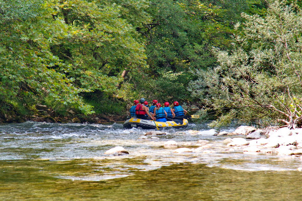 A rafting boat in Voidomatis among the dense vegetation of the river shores.