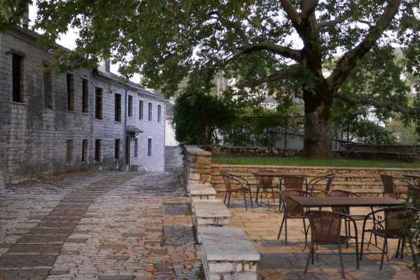 A part of the central square of Vitsa with a cobblestone road, a great platanus tree, and some table with chairs.
