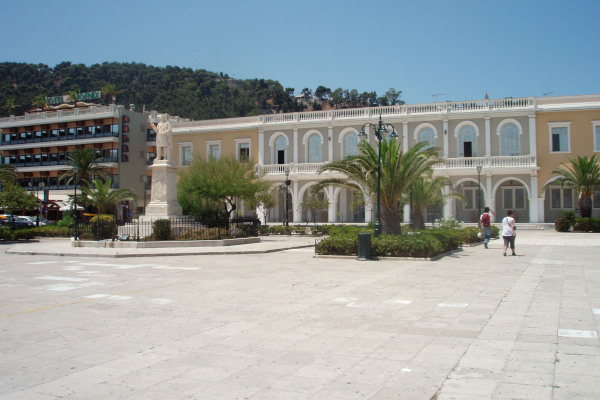 A photo of the Dionysios Solomos Square of Zakynthos Town where the statue of the poet and theater are visible.